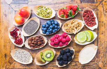 Healthy food berries, fruits, nuts, seeds top view on rustic wood background.Healthy, detox, super food concept.