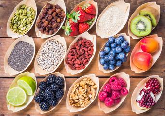 Healthy food, berries, fruits, nuts, seeds top view on rustic wood background.Healthy, detox, super...
