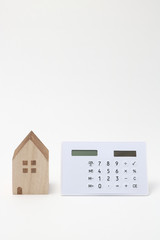 Miniature house and calculator on white background.