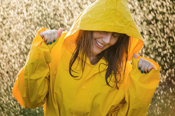 Portrait of happy woman wearing yellow raincoat enjoying the rain.
