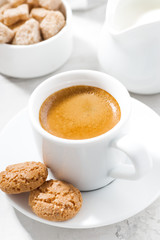 cup of espresso and almond cookies on a white table, closeup