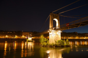 Illuminated Passerelle du College footbridge over the Rhone river in Lyon, France, on a clear evening.