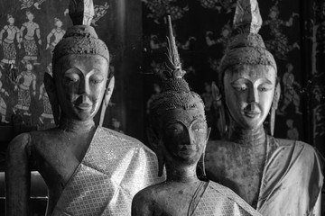 ancient wooden buddha image at wat xieng thong