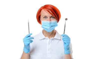 Red headed dental assistant holding two tools