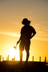 Teen boy silhouette with skateboard at sunset