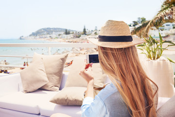 Happy young blond woman taking smartphone photo with smart phone