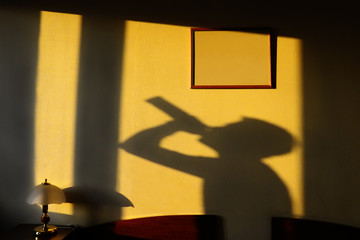 shadow of the alcoholic drinking from a bottle on a yellow wall