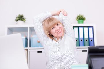 Frau im Büro dehnt Rücken und Schultern