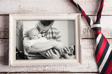 Fathers day composition. Picture frame, photo, tie. Wooden backg