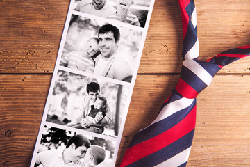 Fathers day composition. Black-and-white photos, tie. Wooden bac