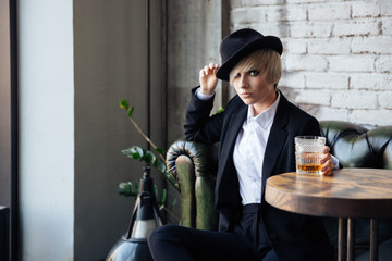 Pretty blonde girl sitting on the couch in a hat