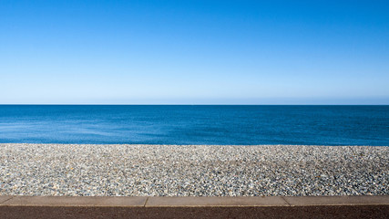 Seascape with pebble stone beach and sea defence wall on a beautiful day in Llandudno Wales UK