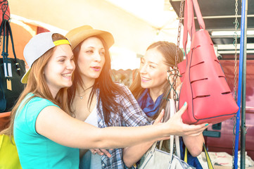 Young women girlfriends at flea market looking for fashion bags - Shopping concept with happy girls having fun together