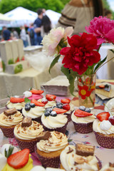 Delicious vanilla cupcake with strawberry frosting and fresh strawberries and blueberries with peonies
