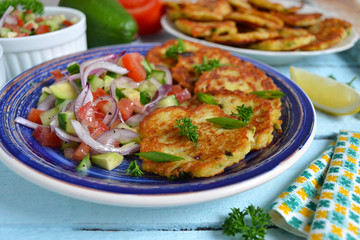 potato pancakes with green onions and sour cream on a wooden bac