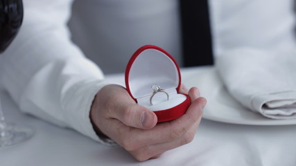 Close up Man holding box with ring making propose to his girlfriend, restaurant