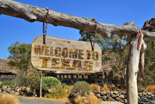 """old wood signboard with text """" welcome to texas"""" hanging on a branch"""