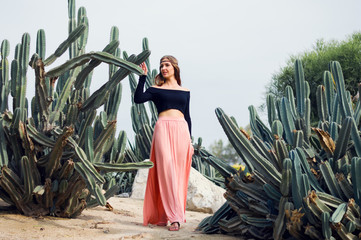 Young woman dressed in hippie clothes standing near big cactus
