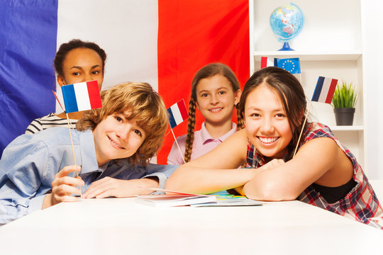 Portrait of happy teenage students holding flags