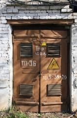 old metal brown doors of old white brick building of transformer