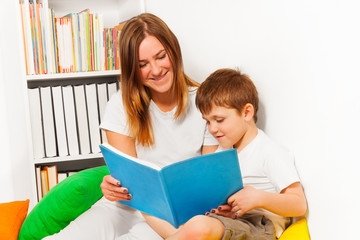 Smiling woman teaching her kid boy to read