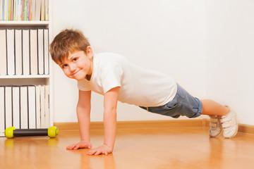 Caucasian preschooler boy making gymnastics