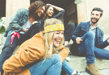 Group of four friends laughing out loud outdoor, sharing good an