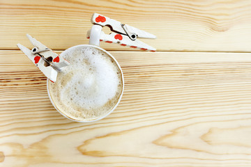 thirst for in love with coffee/ couple craving clothespins gripping the coffee mug with frothy milk foam top view
