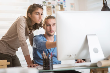 Two young colleagues working on a project on computer