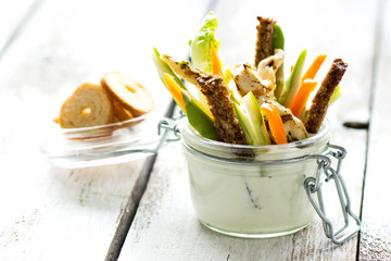 Grilled chicken wings with creamy sauce for dipping with a glass filled with sliced fresh vegetable