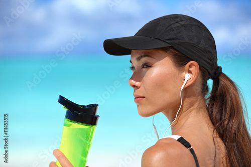 Healthy sporty Asian runner woman running on beach drinking water bottle  listening to music with earbuds bea88acb556