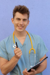 Male doctor pointing at you with pen and holding a notepad or clipboard and wearing medical uniform on blue studio background