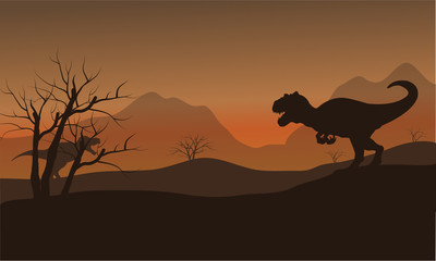 Silhouette of allosaurus in hills at afternoon