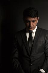 Studio portrait of a serious businessman wearing a black suit