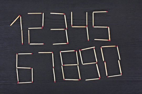 on a black wooden background laid out the numbers of matches from one to zero