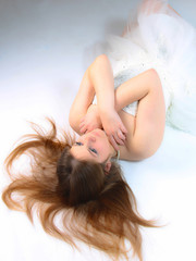 image of a stunning young teenage girl in a white dress lying down with her arms crossed over her chest and her hair spread out over the floor