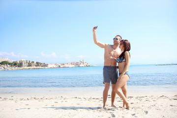 summer love - young couple taking a selfie on the sand
