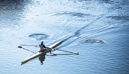 Person sculling in a racing canoe