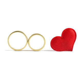 Wedding rings and read heart on white background. Concept for love