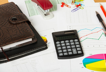 Notebooks, calculator and various stationery items on desktop background.
