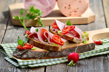 Wurstbrote: Deftiges Landbrot belegt mit Bierschinken rustikal serviert - Slices of Bavarian sausage on farmhouse bread