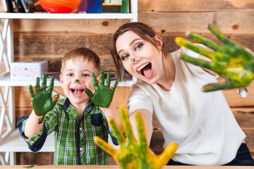 Little boy and mother showing hands painted in colorful paints
