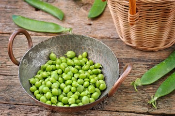 Fresh organic green peas in a basket on a wooden background.
