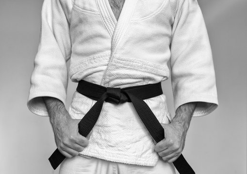 Martial arts Master with black belt in white kimono. Black and white