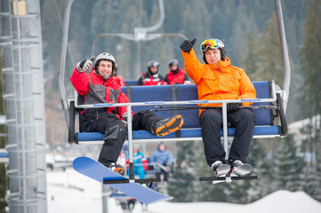 Skier and snowboarder riding up to the top of the mountain on ski lift and showing thumbs up gestures of good class, with an astonishing view nature. Close-up