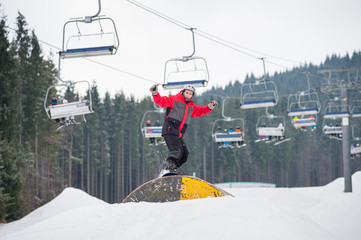 Snowboarder slides down over a hurdle in winter day with snow-covered firs and ski lifts in background at a winter resort