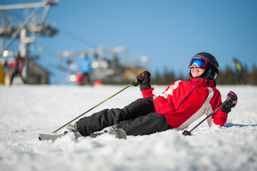 Woman wearing ski goggles, helmet, red jacket, gloves and pants lying with skis on snowy at mountain top and looking away in sunny day with ski lifts and blue sky in background.
