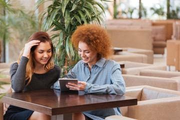 Two smiling women sitting in cafe and using tablet together