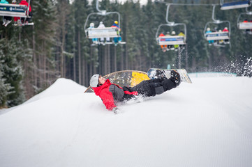 Male snowboarder falls on the slopes during the jumping with ski lifts in background, extreme sport