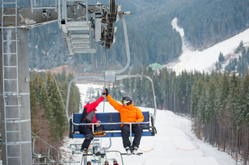 Two male ride the ski chair lift up the mountain together and giving each other a high five, having a fun time. Ukraine, Bukovel